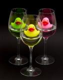 Grüne, gelbe und rosafarbene Gummienten in den Weingläsern stockbilder