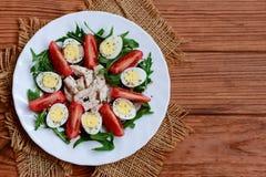 Grüne Gemüsesalat-, Hühner- und Wachteleier Salat mit Tomaten, Arugula, Wachteleiern, Hühnerleiste und Gewürzen auf einer Platte stockbilder