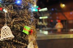 Grüne Geschenkbox mit Lichtern und Glocke auf einem Weihnachtsbaum Stockfotografie