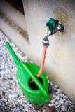 Grüne Gießkanne auf Wasserhahn lizenzfreie stockbilder
