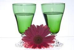 2 grüne Gläser mit rosa Blume Stockfoto