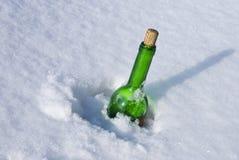 Grüne Glasflasche im Schnee Lizenzfreies Stockfoto