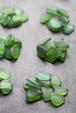 Grüne Glasplatten poliert durch das Meer Stockbild