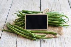 Grüne grüne Bohnen mit einer kleinen Tafel Stockfotografie