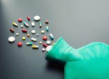 Grüne Gummiwärmflasche mit Pillen Lizenzfreie Stockfotografie