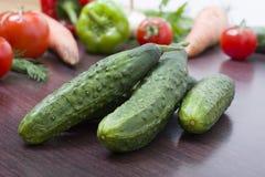Grüne Gurken auf einem Hintergrund des unterschiedlichen Gemüses Frischgemüse auf einem braunen hölzernen Hintergrund Stockfoto