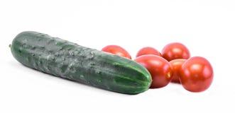 Grüne Gurken und rote Tomaten auf einem weißen Hintergrund - Seitenansicht Lizenzfreies Stockbild
