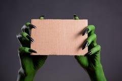 Grüne Hände mit den schwarzen Nägeln, die leeres Stück Pappe halten Stockbilder
