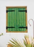 Grüne hölzerne Fensterläden mit schwarzen Eisen-Scharnieren Stockfotografie