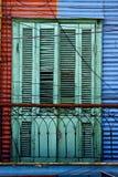 Grüne hölzerne Jalousien und eine rote blaue Wand Lizenzfreie Stockfotos