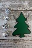 Grüne hölzerne Weihnachtsbaumdekoration auf weißem Hintergrund mit vier Klingelglocken lizenzfreie stockbilder