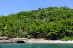 Grüne Hügel durch das Meer Stockfotos