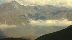 Grüne Hügel und Berge Kaukasus bei schönem bewölktem Sonnenuntergang Die Gergeti-Kirche auf Hintergrund von Bergen stock video