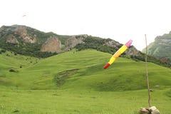 Grüne Hügel und Berge Paradrom Chegem, Gleitschirme im Himmel und ein Stock mit einer gestreiften mehrfarbigen Flagge Lizenzfreie Stockbilder