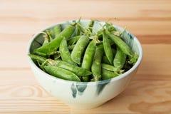 Grüne Hülsen mit Erbsen als Hintergrund Lizenzfreie Stockfotografie