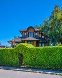 Grüne Hecke mit Bogen über Eingangstor vor Wohnhaus stockfotografie