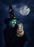 Grüne Hexe mit Kürbis Stockfoto