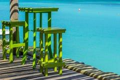 Grüne hohe Tabelle mit zwei Schemeln mit blauem Ozean als Hintergrund Stockfotos