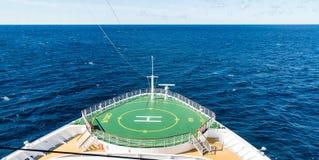 Grüne Hubschrauber-Auflage über blauem Wasser Stockfotos