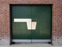 Grüne industrielle Tür im alten Backsteinbau Stockbilder