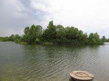 Grüne Insel auf dem See lizenzfreie stockbilder