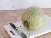 Grüne japanische Melone auf einem weißen Block mit einem Messer in der Küche Stockbild