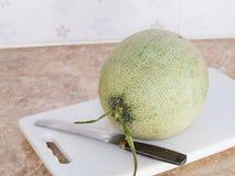 Grüne japanische Melone auf einem weißen Block mit einem Messer in der Küche Lizenzfreies Stockbild