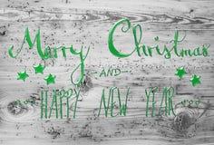 Grüne Kalligraphie-frohe Weihnachten und guten Rutsch ins Neue Jahr, hölzerner Hintergrund Stockfotos