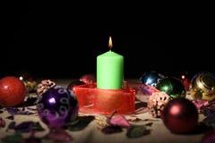 Grüne Kerze mit Weihnachtsdekoration Stockbild