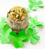 Grüne Kleeblätter und eine Tasche des Goldes Stockbild