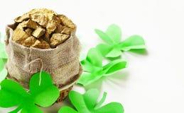 Grüne Kleeblätter und eine Tasche des Goldes Lizenzfreies Stockbild
