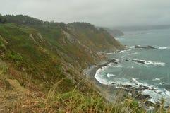 Grüne Klippen mit den Meereswellen, die gegen ihre Felsen an Strand Las Llanas an einem regnerischen Tag brechen 29. Juli 2015 La stockfotos