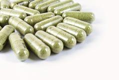 Grüne Kräutermedizinkapsel getrennt Stockfoto
