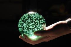 Grüne Kristallkugel an Hand Stockbild
