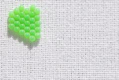 Grüne Kugeln auf weißem Leinen Stockfotos