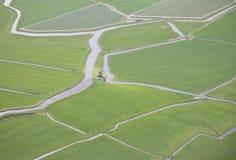 Grüne Landschaft mit Wasser und Windmühle von oben Stockbilder
