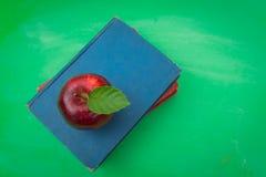Grüne leere Tafel mit rotem Apfel und Buch Stockfotografie