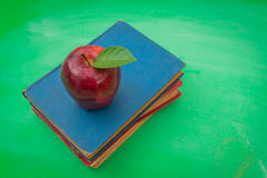 Grüne leere Tafel mit rotem Apfel und Buch Stockbild