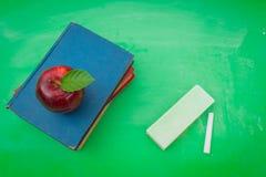 Grüne leere Tafel mit rotem Apfel und Buch Lizenzfreie Stockfotografie