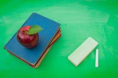 Grüne leere Tafel mit rotem Apfel und Buch Stockbilder