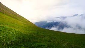 Grüne Lichtung in den Bergen und in den Wolken Stockfotos