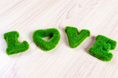 Grüne Liebesbenennung auf dem Bretterboden, gemacht vom künstlichen Gras Stockbild