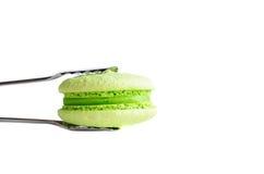 Grüne Makrone gehalten durch Gebäckzangen Lizenzfreies Stockfoto