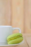 Grüne Makrone, Macaron mit Schale auf hölzernem Hintergrund Stockfotografie