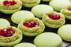 Grüne Makronen mit Pistazien ganache Creme und Himbeeren Co Stockfotografie