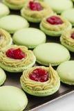 Grüne Makronen mit Pistazien ganache Creme und Himbeeren Co Lizenzfreies Stockfoto