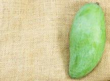 Grüne Mango der Nahaufnahme auf Juteleinwandsackbeschaffenheit Stockfoto