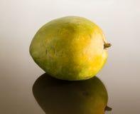 Grüne Mangofrucht auf Spiegel mögen Oberfläche Stockfotografie