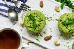 Grüne matcha und Bananenrohe Käsekuchen strengen Vegetariers mit Minze und Nüssen über weißem Holztisch mit Tasse Tee und Löffel Lizenzfreie Stockfotos