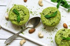 Grüne matcha und Bananenrohe Kuchen strengen Vegetariers mit Minze und Nüssen über weißem Holztisch mit einem Löffel Stockfotos